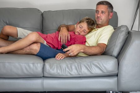 A shot of a sleepy young boy lying down on a couch watching tv with his dad, they are wearing casual clothing.