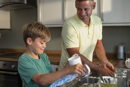 A side-view shot of a young boy and a father washing the dishes together. Stockfoto