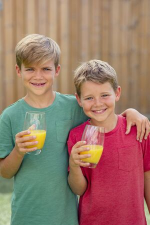 A front view shot of two young boys smiling and looking at the camera, they is holding a glass of orange juice.
