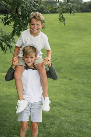A shot of two young boys playing together, one boy is sitting on his brothers shoulders. Stockfoto