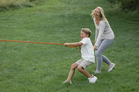 A side view shot of a young boy and his mother playing tug a war together.
