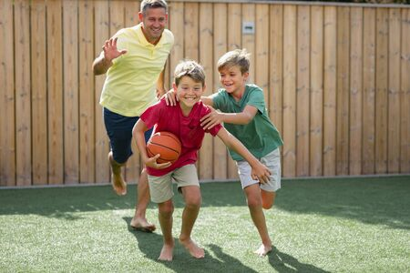 A front-view shot of a family of boys playing with a basketball in the back yard.