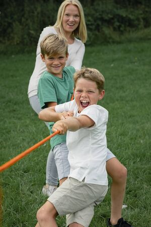 A front view shot of two young boys and their mother playing tug a war together.