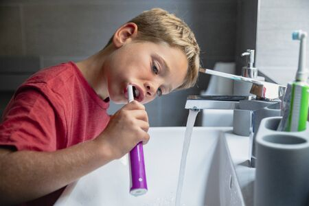 A side view shot of a young boy brushing his teeth at the sink. Stockfoto