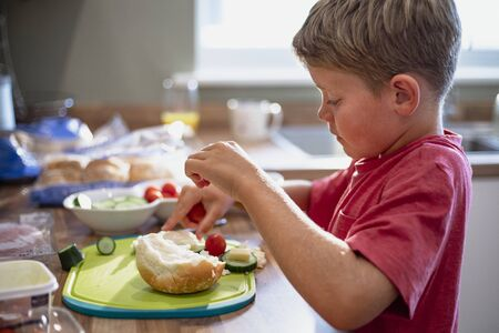 A side view shot of a young boy making himself a sandwich in the kitchen.