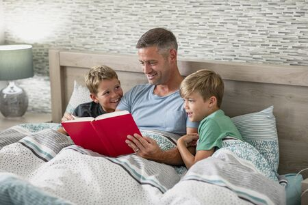 A shot of a father reading a book to his two young sons in bed. Stockfoto