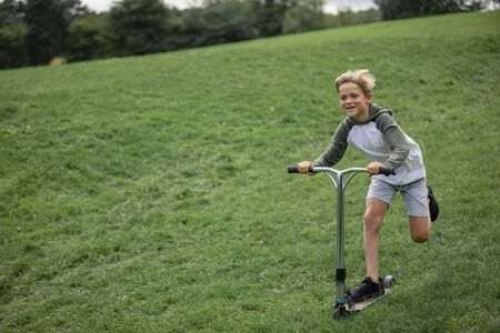 A front view shot of a young boy playing on push scooter going down a hill.