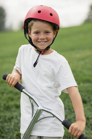 A front view portrait shot of a young boy playing on push scooter. Stockfoto
