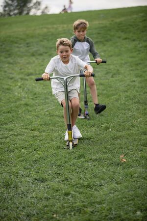 A front view shot of two young boys playing together on push scooters going down a hill.