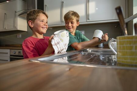 A side-view shot of two young brothers washing the dishes together.