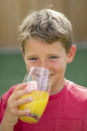 A front view shot of a young boy smiling and looking at the camera, he is holding a glass of orange juice.