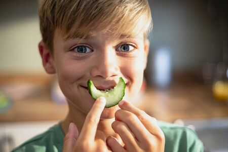 A front view shot of a young boy smiling and looking at the camera, he is holding a slice of cucumber over his mouth.