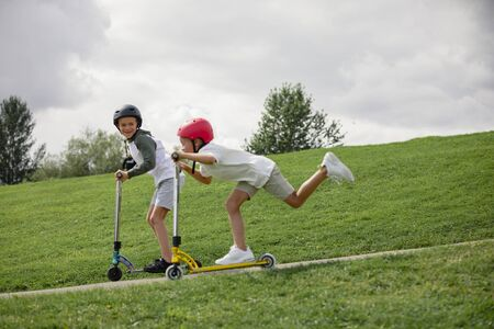 A shot of two young boys playing together on push scooters.