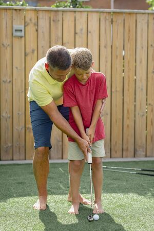 A front-view shot of a father teaching his young son how to play golf.