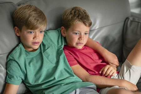 A shot of two young brother's sitting down on a couch together watching tv, they are wearing casual clothing.