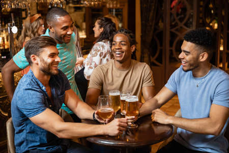 A group of male friends having a beer together at a bar.