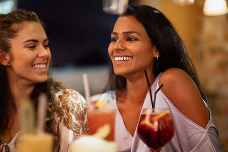 Two women sitting at a bar laughing while having a drink.