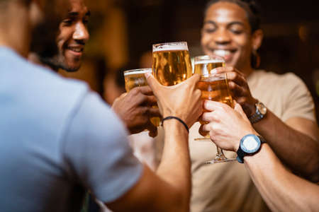 A group of male friends having a celebratory toast togetherat a bar. Stockfoto