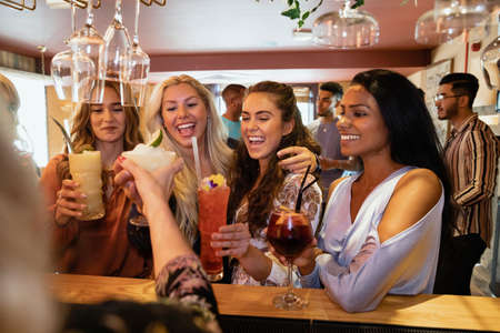 A group of female friends standing at the bar together and toasting. Stockfoto