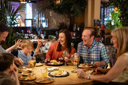 A family having a meal at a restaurant. A young boy is making them all laugh by making a face using food.