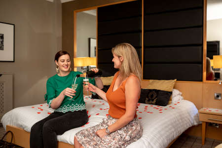Two caucasian women drinking champagne, celebrating and having fun together on a hotel bed in Jesmond, England.