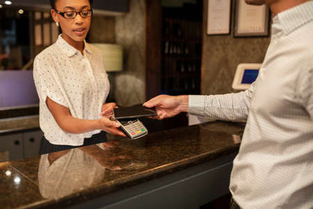 A female hotel receptionist taking the contactless payment of a customer who is checking in to the hotel, he is using his smart phone to pay.
