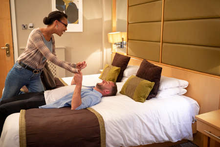 A multi-ethnic couple being playful in a hotel room, they have a romantic evening planned.
