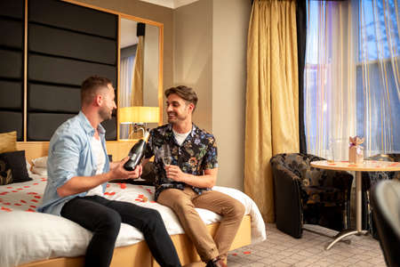 Two caucasian men drinking champagne, celebrating and having fun together on a hotel bed in Jesmond, England. Stockfoto