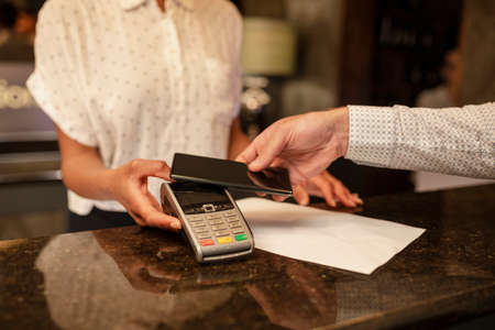 An unrecognisable female hotel receptionist taking the contactless payment of a customer who is checking in to the hotel, he is using his smart phone to pay.