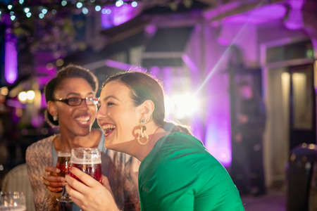 Diverse female friends drinking alcohol outdoors at a bar/restaurant, celebrating and having fun together.