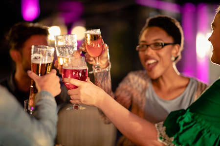 Group of diverse friends drinking champagne outdoors at a bar/restaurant, celebrating and having fun together. Stockfoto - 156777671