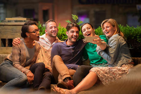Group of diverse friends taking a selfie on a smart phone outdoors at a bar/restaurant, they are celebrating and having fun together. Stockfoto