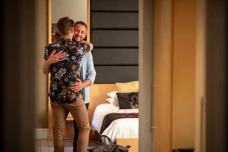 Two caucasian men embracing in a hotel room, they have a romantic evening planned. Stockfoto