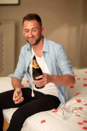 A caucasian man opening a bottle of champagne, he is wearing casual clothing and sitting on a hotel bed in Jesmond, England.