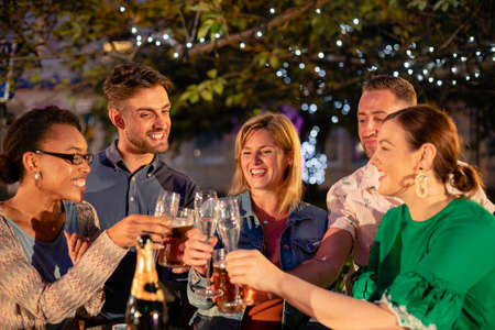 Group of diverse friends drinking champagne outdoors at a bar/restaurant, celebrating and having fun together. Stockfoto