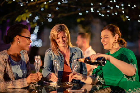 Group of diverse female friends drinking champagne outdoors at a bar/restaurant, celebrating and having fun together.