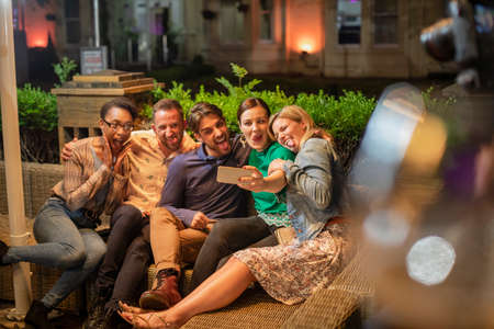 Group of diverse friends taking a selfie on a smart phone outdoors at a bar/restaurant, they are celebrating and having fun together, they are making silly faces.
