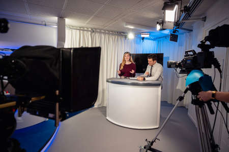 A TV show in the process of being filmed in a studio. The presenters are sitting at the studio desk, talking to the camera.