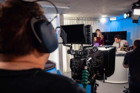 Over the shoulder view of a TV show in the process of being filmed in a studio. The presenters are sitting at the studio desk, talking to each other, while the camera man is preparing to start filming again. Stockfoto - 156897371