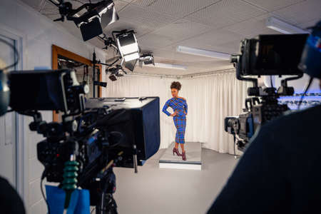 A TV show being filmed in a studio. A women is modelling a dress during the fashion segment. It is shot in between two film cameras. Stockfoto - 156897422