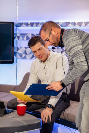 A TV show in the process of being filmed in a studio. The producer is holding a clipboard and showing the presenter his notes and ideas for the next segment. They are preparing to start filming again. Stockfoto