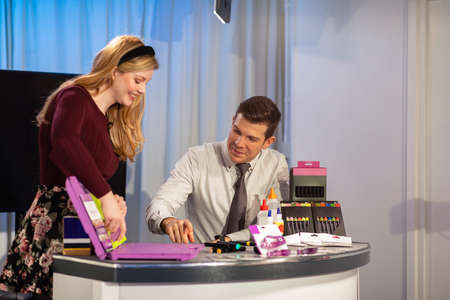 A TV show in the process of being filmed in a studio. The presenters are at the studio desk, selling art supply to the viewers. Stockfoto