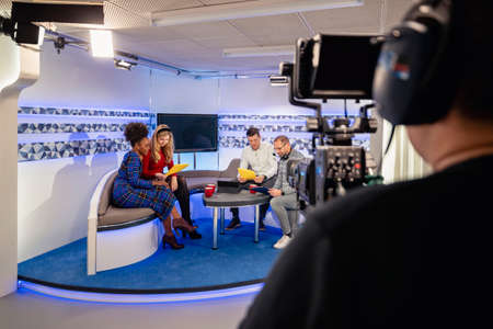 Over the shoulder view of a TV show in the process of being filmed in a studio. The presenters are sitting on the studio sofa while looking at notes and talking to the producer, while the camera man is preparing to start filming again.