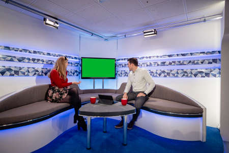 A TV show in the process of being filmed in a studio. The presenters are sitting on the studio sofa while looking at the television behind them, discussing it to their viewers. Stockfoto