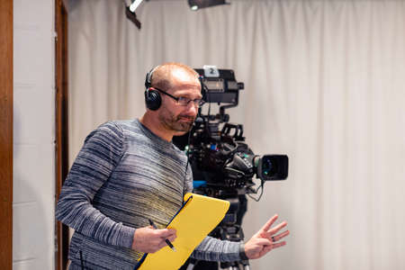A producer of a TV show, wearing a headset, standing next to a film camera in a film studio. He is gesturing to the presenters how many seconds they have until they go live.