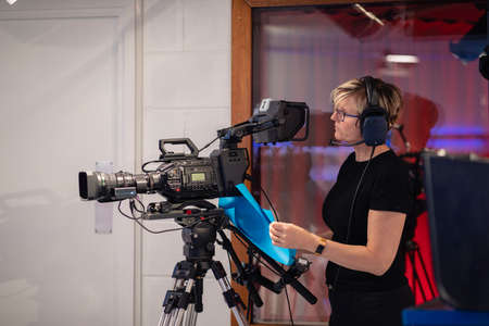 Side view of a camerawoman, wearing a headset looking through the film camera viewfinder while filming a TV show. Stockfoto