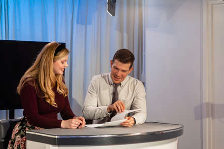 Two TV hosts sitting at a desk in a film studio. They are reading the show notes together, preparing to start filming again. Stockfoto