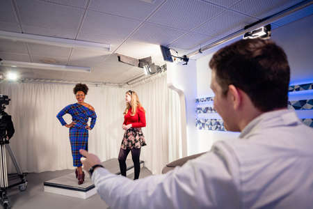 Over the shoulder view of a TV show being filmed in a studio. A woman is modelling clothing during the fashion segment while the presenters stand near to her and discuss it. Stockfoto