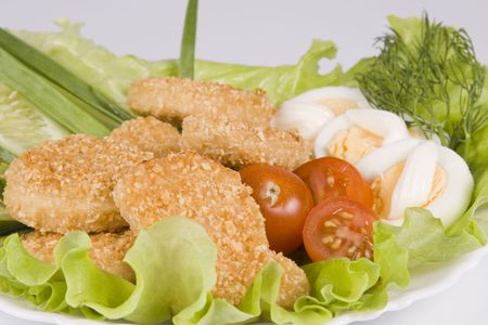 Appetizing fried chicken nuggets, egg with mayonnaise, tomatoes, cucumbers and onions on salad leaves. Close-up. Selective focus. Stock Photo - 2592438