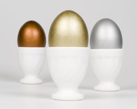 eggcup: Gold, silver and bronze eggs in a white eggcup. Concept for first place. Over a white background.